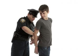 Policeman handcuffing teenager
